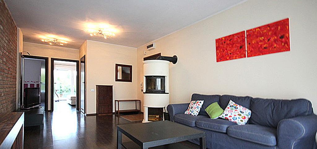 na zdjęciu luksusowy salon z kominkiem w apartamencie na wynajem w Szczecinie