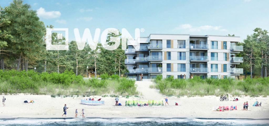 na zdjęciu luksusowy apartamentowiec nad morzem, w którym znajduje się oferowany apartament na sprzedaż