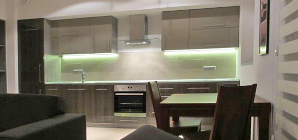 zdjęcie przedstawia aneks kuchenny widziany z perspektywy salonu w apartamencie na wynajem w Katowicach