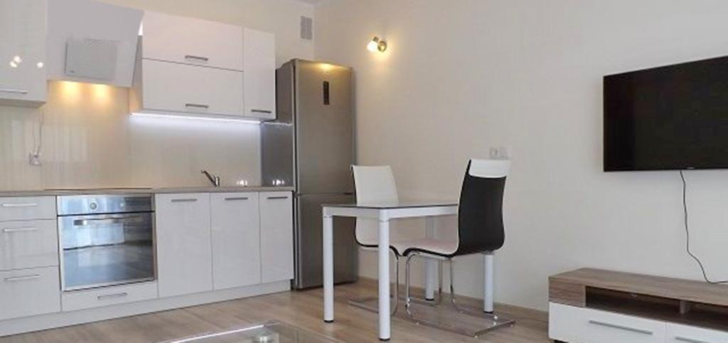 na zdjęciu widok z salonu na aneks kuchenny w luksusowym apartamencie do wynajęcia w Słupsku