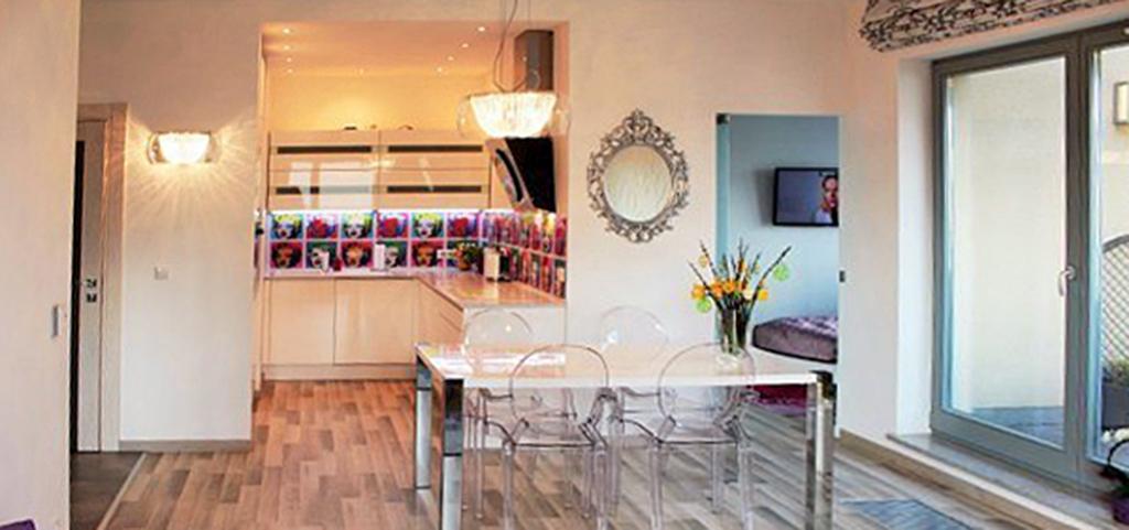 na zdjęciu salon i aneks kuchenny w oddali w luksusowym apartamencie do sprzedaży w Szczecinie