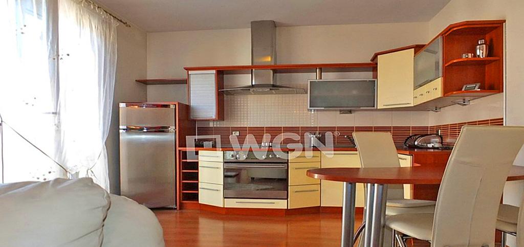 zdjęcie prezentuje widok z salonu na aneks kuchenny w apartamencie do wynajęcia w Katowicach