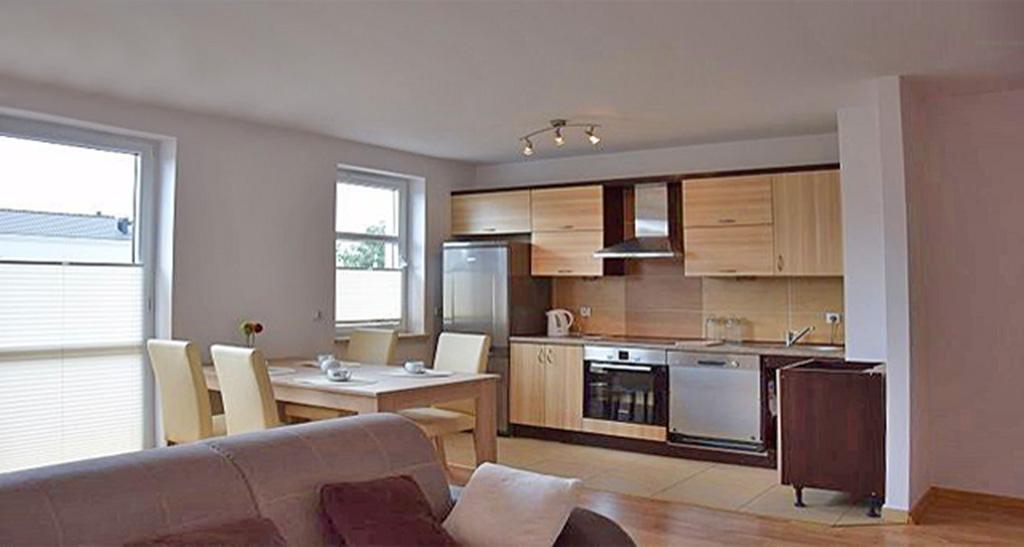na zdjęciu widok z salonu na aneks kuchenny w apartamencie do sprzedaży w Słupsku