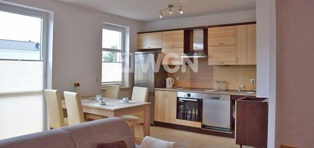 zdjęcie prezentuje widok z salonu na luksusowo wyposażony aneks kuchenny w apartamencie do wynajęcia w Słupsku