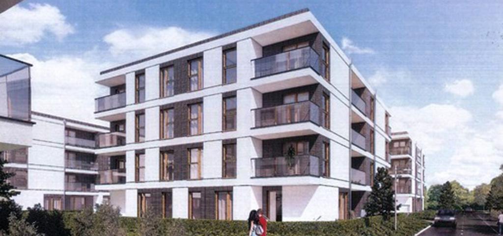 na pierwszym planie apartamentowiec w okolicy Poznania, w którym sprzedawany jest luksusowy apartament