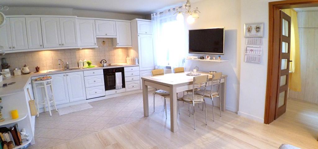 na zdjęciu salon, aneks kuchenny oraz jadalnia w luksusowym apartamencie do sprzedaży w Inowrocławiu